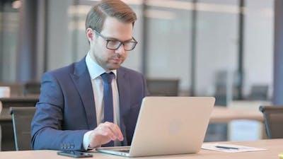 Successful Businessman Celebrating on Laptop at Work