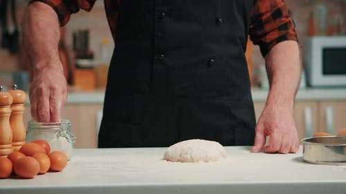 Man Sifting Flour on Dough