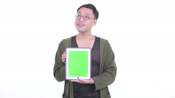 Thumbnail for Happy Japanese Man with Eyeglasses Thinking While Showing Digital Tablet