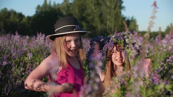 Beautiful Happy Girls Dancing on Blossoming Field at Summertime