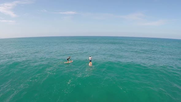 Aerial view of two men sup stand-up paddleboard surfing in Hawaii