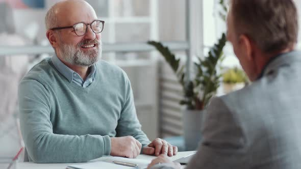 Thumbnail for Joyous Senior Man Talking with Business Partner at Office Table