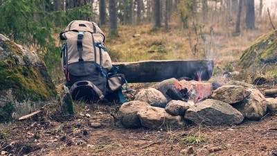 Backpack and campfire in the forest