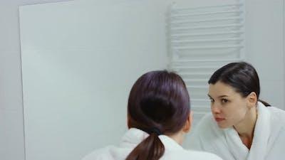 Charming Woman in Bathrobe Looking at Mirror