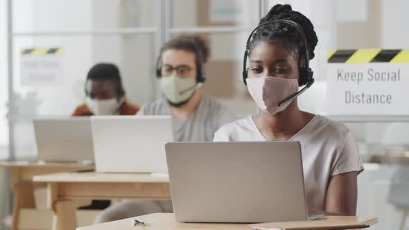 Thumbnail for Black Woman in Face Mask Working on Laptop in Office of Call Center