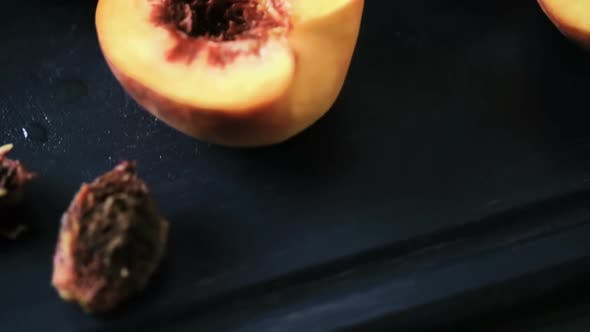 Cutting peaches in half for making grilled peaches.
