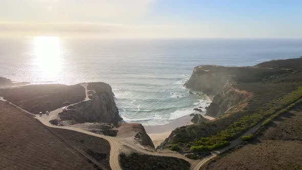 Aerial view of bay protected by high cliffs during sunset
