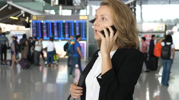 Thumbnail for Young Businesswoman In Business Trip Speaking On Smartphone In Airport