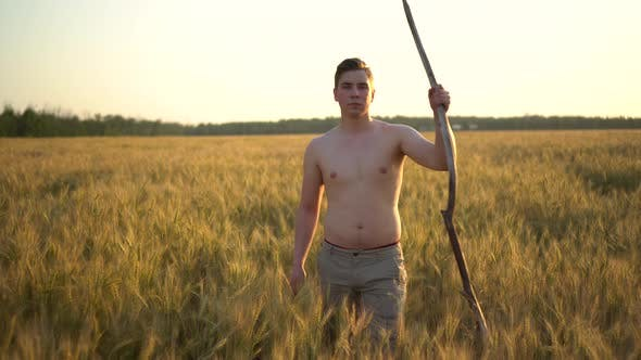 A Shirtless Young Man Is Walking Along a Wheat Field with a Stick in His Hand. Man in a Yellow Field