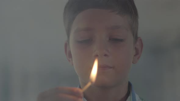 Thumbnail for Close-up Portrait of Little Boy Playing with the Matches in the Dark Smoky Room