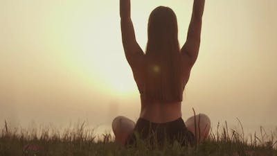 Woman is Engaged in Meditation on the Background of Sunset