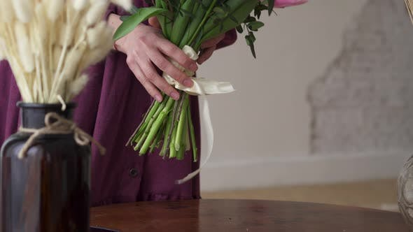 Woman Florist Puts a Finished Bouquet on the Table.