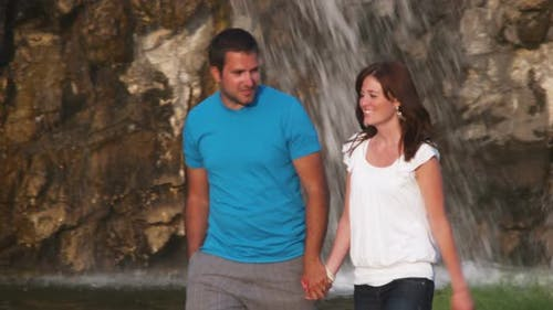 Couple walking in front of a waterfall in a garden.