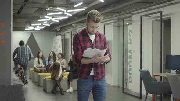 Thumbnail for Thoughtful Blond Young Man Studying Papers Documents Standing in the Modern Office. Female