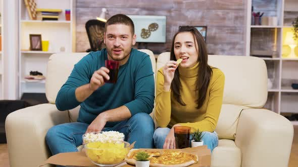 Thumbnail for Couple Sitting on Couch Laughing While Watching Tv and Eating Pizza