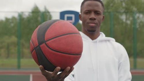 Basketballspieler posiert auf dem Außenplatz