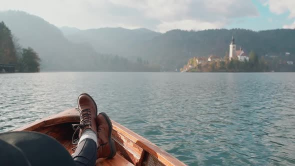 Thumbnail for First Person View of Female Feet in Brown Boots in Wooden Boat Floating on Lake at Sunset. The Girl