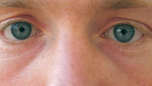 Thumbnail for Close Up of Sad Male Blue Eyes Blinking and Looking Into Camera with Daylight. Portrait of Young