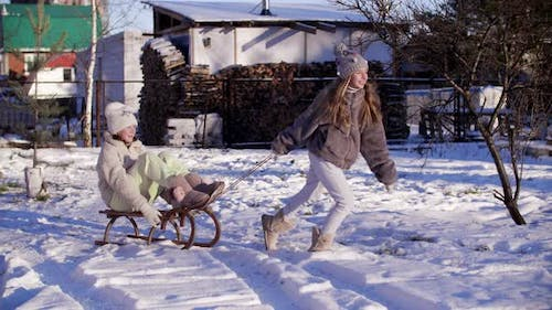Playful Girl Riding Girlfriend on Sledge on Snowy Countryside on Holiday Vacations. Laughing