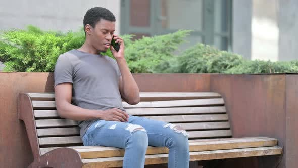 Upset Young African Man Angry on Smartphone on Bench
