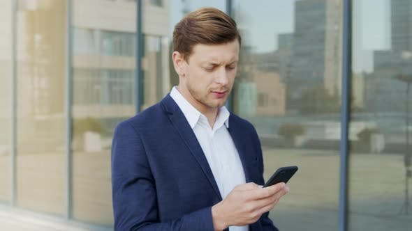Thumbnail for Businessman Using Smartphone at Street. Entrepreneur Texting on Mobile Phone