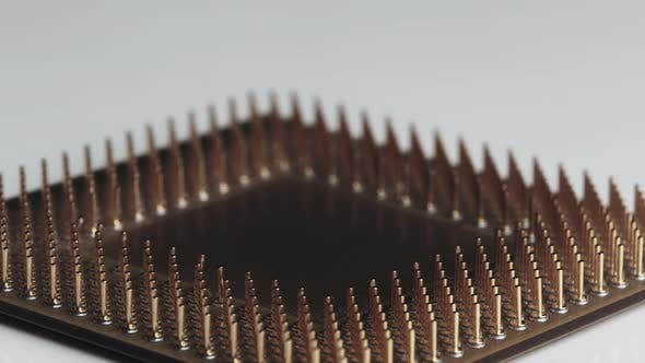 The Computer Processor CPU with Gold Plated Contacts Spins on White Background