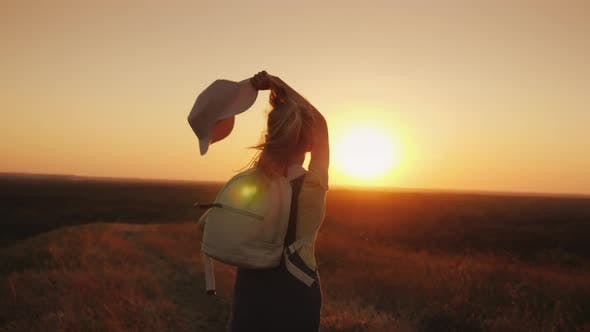 Cover Image for The Long-haired Girl Runs Along the Country Road and Wags Her Hat. Enjoy the Warmth, Summer