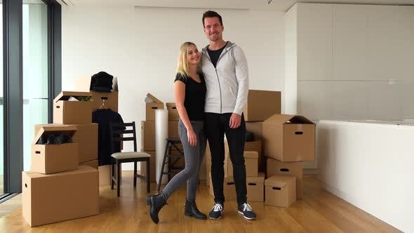 Thumbnail for A Happy Moving Couple Stands in an Empty Apartment and Smiles at the Camera - Cardboard Boxes