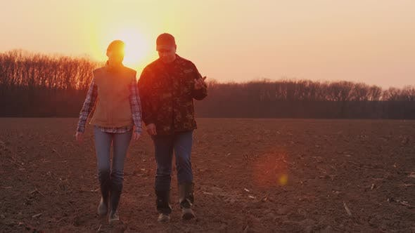 Thumbnail for Two Farmers, a Man and a Woman Walking Along a Plowed Field