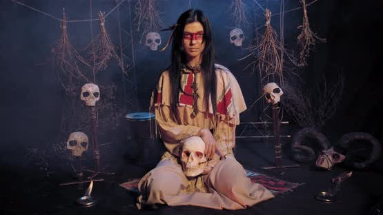 Indian Woman with Red Paint on Her Face Is Sitting on the Ground with a Skull