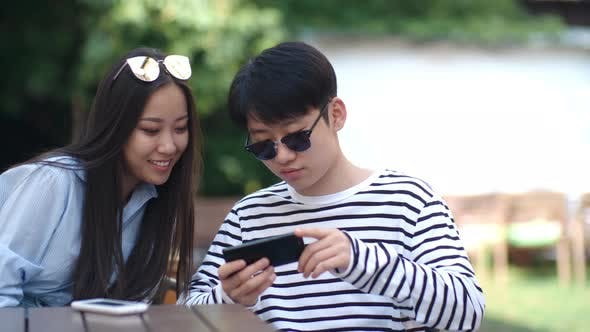 Thumbnail for Joyous Teenage Boy and Girl Using Smartphone in Outdoor Cafe