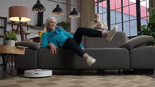 Happy Aged Woman Turning on Robot Vacuum Cleaner