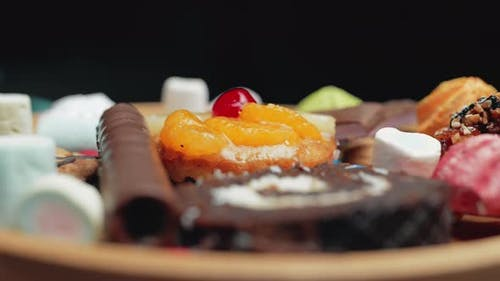 A Sweets and Colorful Candy are Rotating on the Plate
