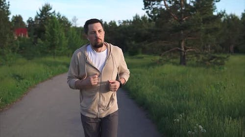 Man Who Is Engaged in Sports Running Is Preparing for a Sprint in the Park Area