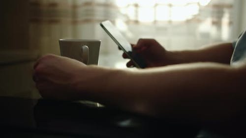 Men's Hands Sits at a Glass Table Drinks Coffee and Uses a Mobile Phone