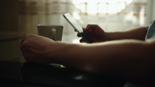 Herrenhände sitzt an einem Glastisch, trinkt Kaffee und benutzt ein Handy