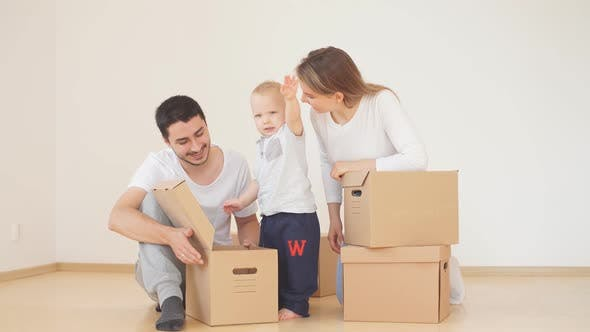 Family with Boy Unpacking Moving Cardboard Boxes at New Home