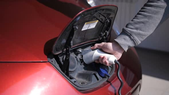 Thumbnail for Male Hand Unplugging Electric Car Charging Cord