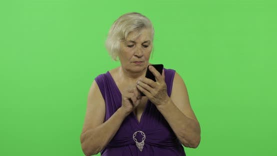Thumbnail for An Elderly Woman Talks on a Smartphone. Old Grandmother Smiles. Chroma Key