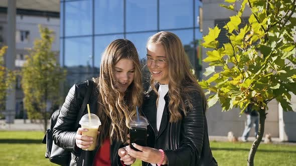 Cover Image for Two Young Smiling Women Browsing Internet on Mobile Phone