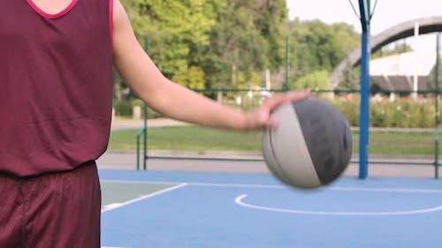 Teenager spielt mit Basketball auf Spielplatz im Freien. Guy Bangs Ball auf dem Boden. Ball und Torso
