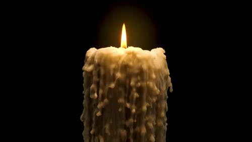 An old and melted candle rotates in front of a black background
