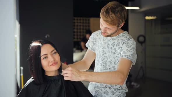 Beautiful Brunette Woman Customer Laugh in a Beauty Salon While Talking To Young Male Hairdresser