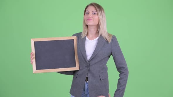 Thumbnail for Happy Young Blonde Businesswoman Holding Blackboard and Giving Thumbs Up