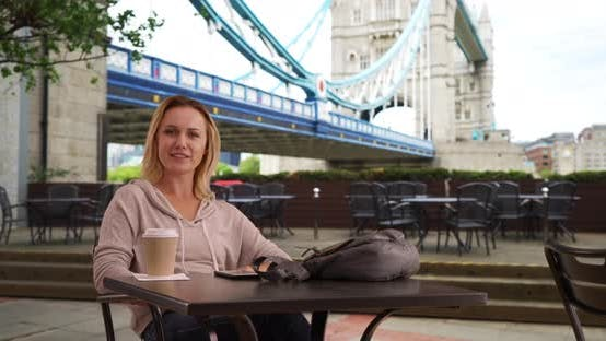 Charming white female sitting at outdoor cafe near London smiling at camera