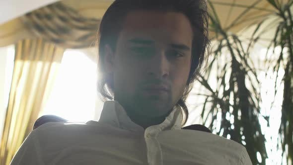 Thumbnail for Young Handsome Man with Long Brown Hair Looking in Camera at Home