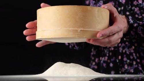 sifting flour. woman sifting flour through sieve