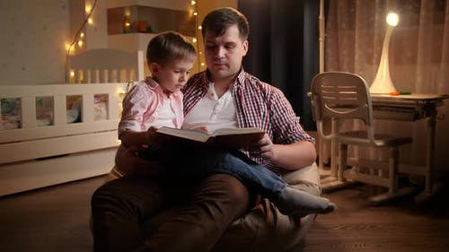 Smiling Little Boy Listening To Bedtime Story His Father Is Reading To Him at Night