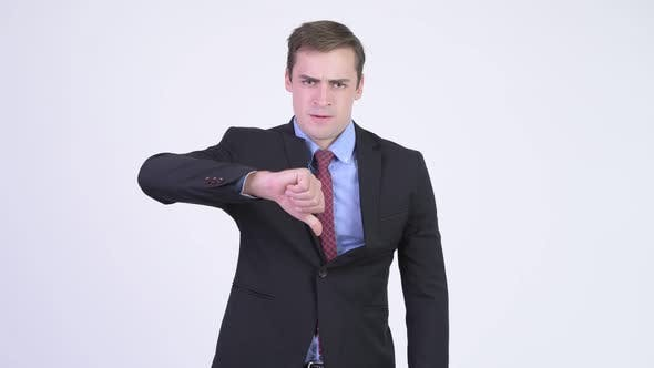 Cover Image for Young Stressed Businessman Looking Angry While Giving Thumbs Down
