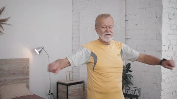 Thumbnail for Alter gutaussehender Mann führt einen gesunden Lebensstil und macht nützliche Übungen für Gesundheit und Vitalität im Raum